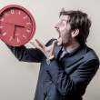 Businessman with clock screaming — Stock Photo