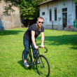 Hipster modern stylish blonde man with bike — Stock Photo #26996481