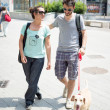 Couple with dog walking in the street — Stock Photo #27393441