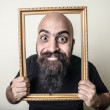 Funny bearded man with golden frame — Stock Photo #27402497