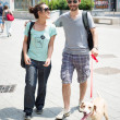 Couple with dog walking in the street — Stock Photo #27403025