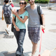 Couple with dog walking in the street — Stock Photo #27515929