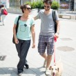 Couple with dog walking in the street — Stock Photo