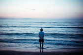 Man back to the sea at sunset — Stock Photo