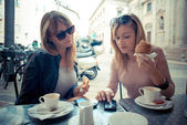Two beautiful blonde women talking at the bar — Stock Photo
