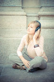 Beautiful blonde woman listening to music — Stock Photo