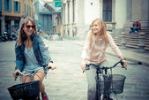 Two beautiful blonde women shopping on bike — Stock Photo