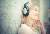 Beautiful blonde woman listening to music — Stockfoto