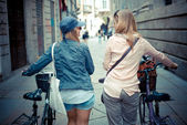 Two beautiful blonde women shopping on bike — Stock Photo
