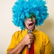 Crazy funny young man with blue wig — Stock Photo