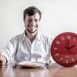 Young stylish man with white shirt holding red clock — Stock Photo