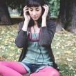 Young beautiful woman listening to music autumn — Foto Stock