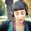 Beautiful young woman listening to music — Stock Photo