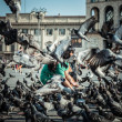 Woman playing with flying pigeons in milan piazza duomo — Stock Photo