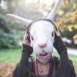 Rabbit mask woman listening to music — Stock Photo
