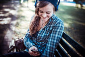 Beautiful young blonde hipster woman listening music — Stock Photo