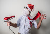 Funny santa claus babbo natale with hairdryer — Stock Photo