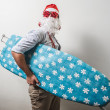 Funny santa claus babbo natale ironing surfer — Stock Photo
