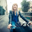 Beautiful blonde woman on bike — Stock Photo