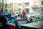 трое друзей женщина в баре с помощью телефона — Стоковое фото