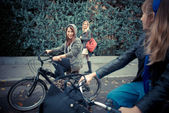 Three friends woman on bike — Stock Photo