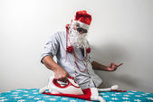 Funny santa claus babbo natale ironing — Stock Photo