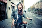 Beautiful red head woman on bike — Stock Photo