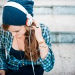 Beautiful young blonde hipster woman listening music — Stock Photo #36124133
