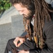 Stylish elegant dreadlocks businessman listening music — Stock Photo