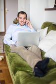 Elegant business multitasking multimedia man at home — Stock Photo