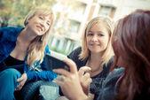 Three friends woman at the bar using phone — Stock Photo