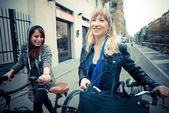Two friends woman on bike — Stock Photo