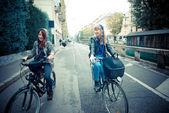 Two friends woman on bike — Stock Photo