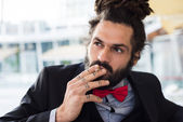 Stylish elegant dreadlocks businessman smoking — Stock Photo
