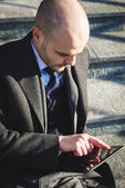 Successful elegant fashionable businessman using tablet — Stock fotografie