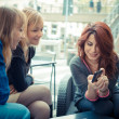 Three friends woman at the bar using phone — Stock Photo
