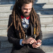 Stylish elegant dreadlocks businessman listening to music — Stock Photo