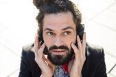 Stylish elegant dreadlocks businessman listening to music — Stock Photo