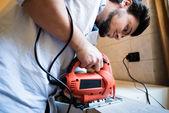 Bricolage jovem trabalhando serrar — Fotografia Stock