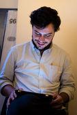 Glad fotograf. ung man i polotröja innehar digital kamera och tittar över axeln när man står i studio med belysning utrustning på bakgrund — Stockfoto