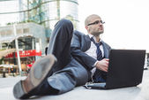 Successful elegant fashionable businessman using tablet — Stock Photo
