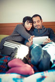 Couple in love on the bed using tablet — Stock Photo