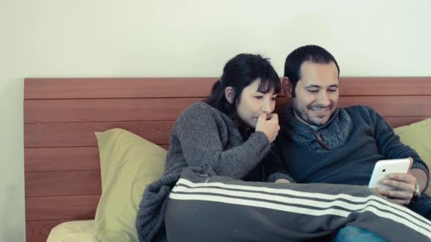 Par usando la tableta en la cama en su casa — Vídeo de stock