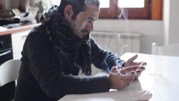 Joven usando la tableta y fumando — Vídeo de stock