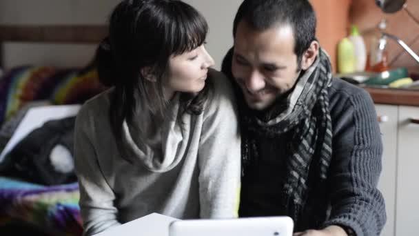 Par usando la tableta sonriendo y besos — Vídeo de stock