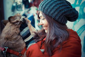 Beautiful woman red coat hugging the dog — Stock Photo