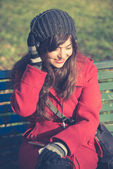 Beautiful woman red coat listening music — Foto Stock