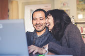 Couple in love using notebook at home — Stockfoto