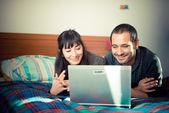 夫妇在床上使用笔记本的爱情 — 图库照片
