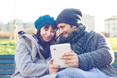 Couple in love using tablet at the park — Stock Photo